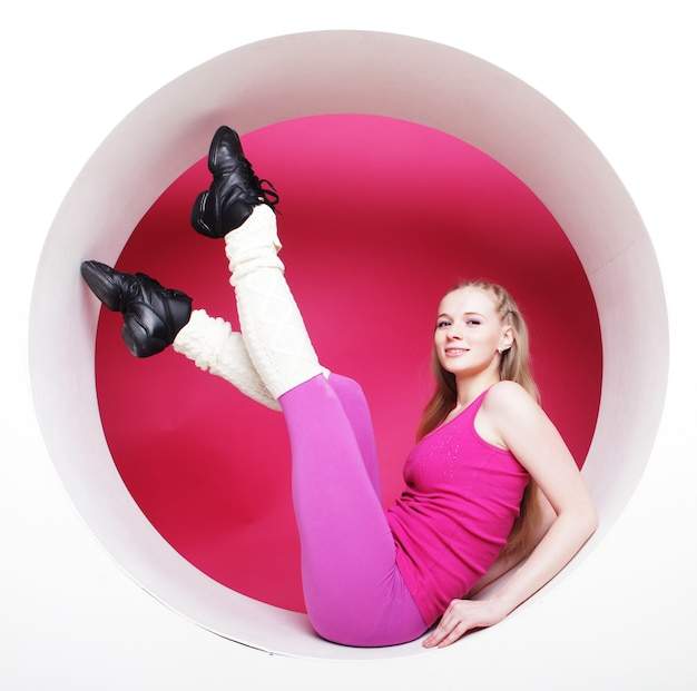 Sporty woman posing in pink circle