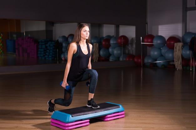 Спортивная женщина практикует на степ-платформе в тренажерном зале