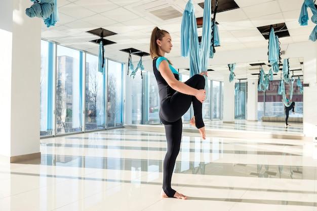 Йога мухи спортивной женщины практикуя как утренняя зарядка в тренажерном зале.