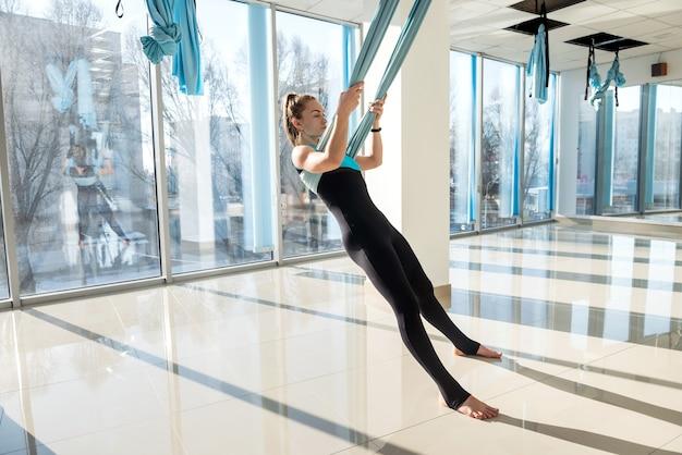 フィットネスジムで朝のエクササイズとしてフライヨガを練習しているスポーティな女性。