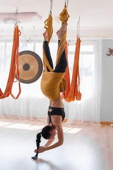 Спортивная женщина практикует летать йогу, висящую в тренажерном зале вверх ногами