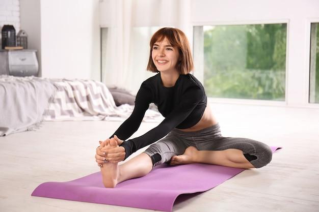 Спортивная женщина упражнениями йоги дома