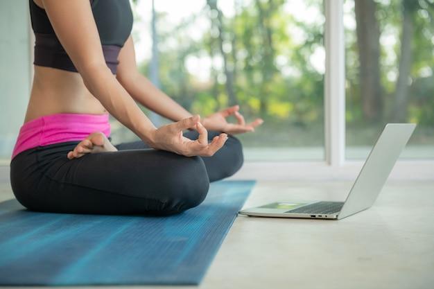 Donna sportiva che pratica yoga, fa esercizio ardha padmasana, medita nella posa del loto, si allena, indossa abbigliamento sportivo, guarda tutorial video fitness online sul laptop, fa allenamento a casa seduta