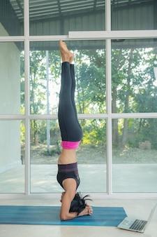 Donna sportiva che pratica yoga, fa esercizi in verticale, posa di salamba sirsasana, allenandosi, indossando abbigliamento sportivo nero, guardando video tutorial di fitness online sul laptop, facendo allenamento a casa seduti.