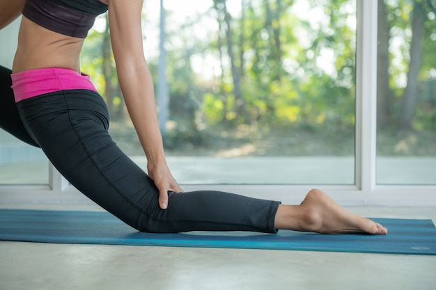 Sporty woman practicing yoga, doing horse rider exercise, anjaneyasana pose, working out, wearing sportswear, black pants, doing workout at home sitting.