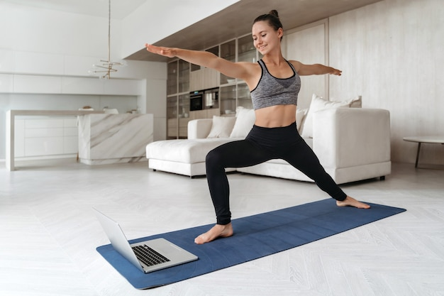 Sporty woman practicing yoga at home because of social distancing, using laptop for online class