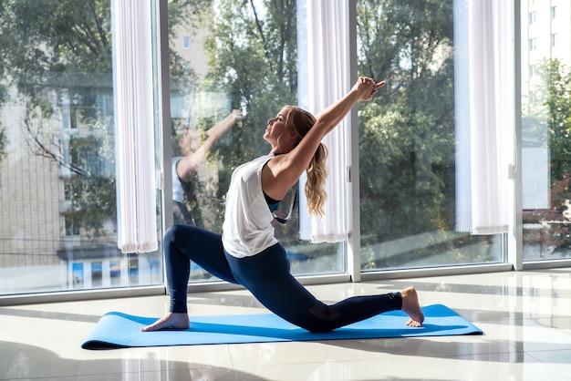 Спортивная женщина расслабляется, тренируясь на коврике для йоги, реабилитации фитнеса. здоровый образ жизни