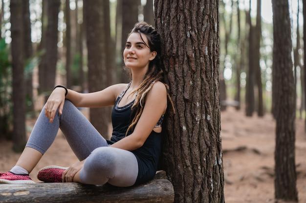 Спортивная женщина отдыхает сидя на деревьях