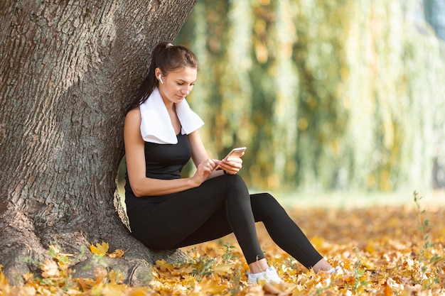 Sporty woman resting close to a tree