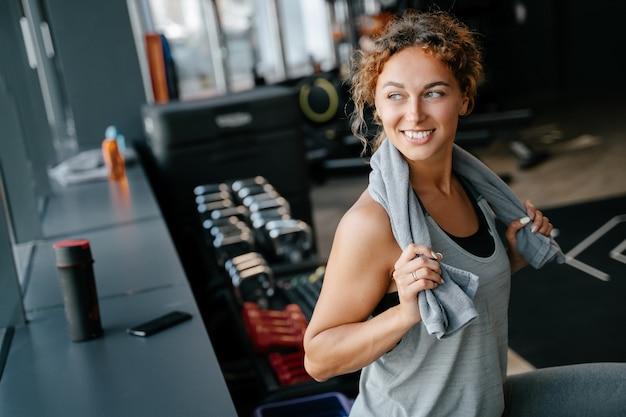 スポーティな女性はジムでのトレーニングの後に休憩し、窓の外を見て笑顔を見せます。横向きのポートレート。健康的なライフスタイルのコンセプト。