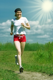 Sporty woman running on field road under blue sky with clouds