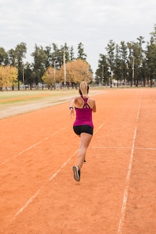 Sporty woman running on stadium track