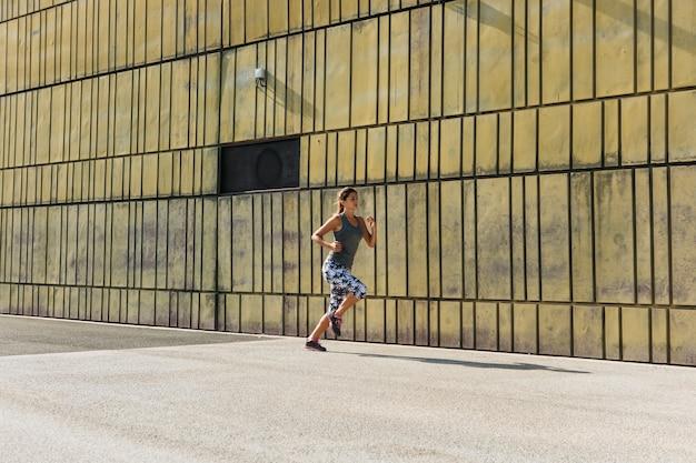 Donna sportiva che funziona nell'ambiente urbano