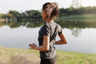 Sporty woman running with lake background