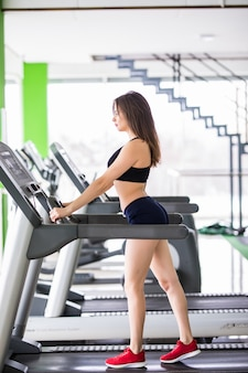 Sporty woman runs on sport simulator in modern fitness centre dressed up in black sportswear