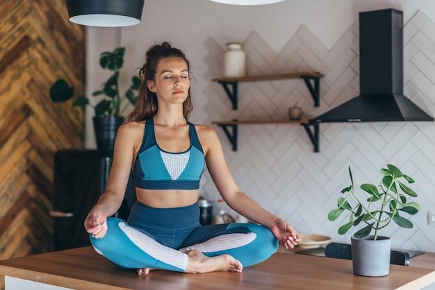 スポーティな女性は目を閉じてテーブルに座って瞑想します。