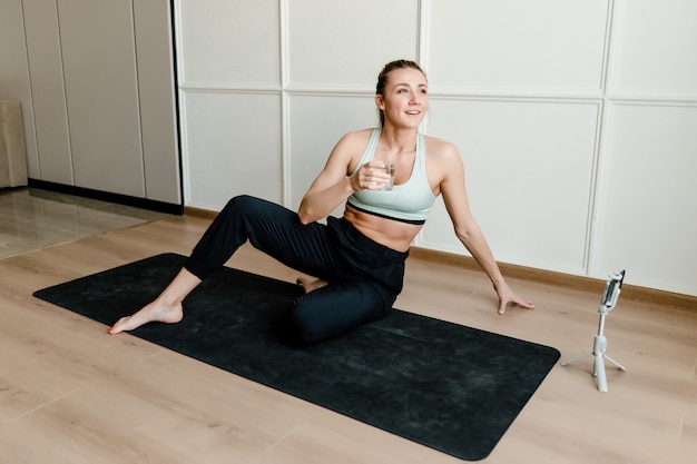 Sporty woman sitting on yoga mat at home with phone online
