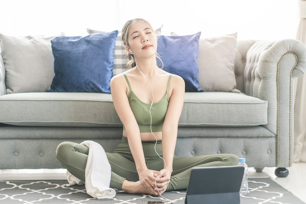 A sporty woman in sportswear exercises while watching online exercise session on her smart phone at home