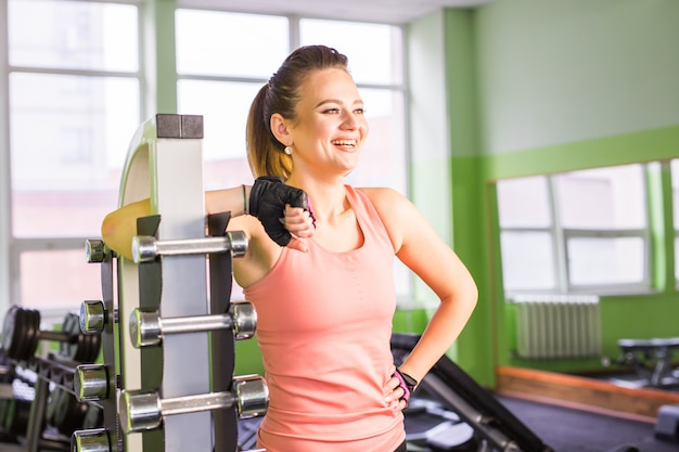 Sporty woman standing in fitness gym near the shelf with dumbbells