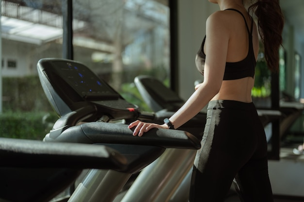 A sporty woman standing on treadmill at gym. fitness concept, healthy, sport, lifestyle