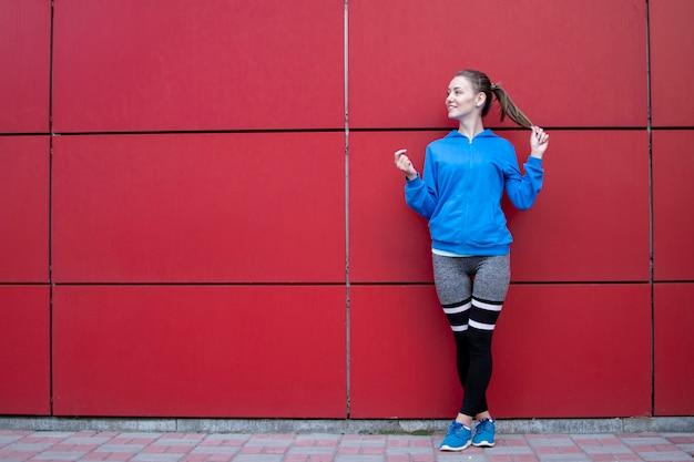 スポーティな女性はスポーツウェア、街の通り、コピー領域でポーズをとってフィットネス女性の赤い壁に立ちます