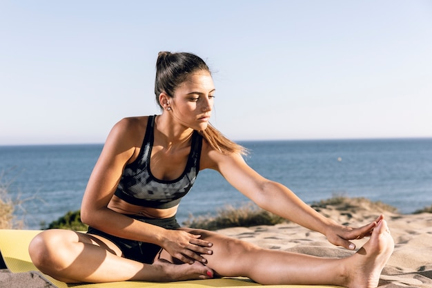 Sporty woman stretching on fitness mat