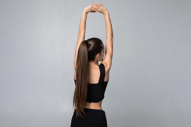 白い壁に分離された彼女の腕を伸ばしてスポーティな女性