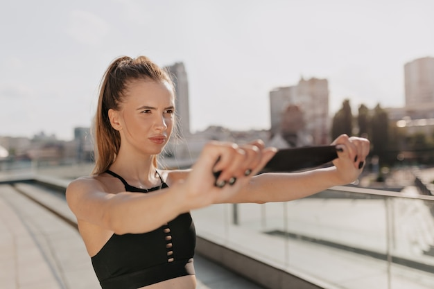 Sporty woman stretching her arms and looking concentrated in outdoor in the city