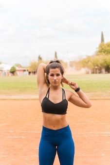 Sporty woman stretching on stadium track