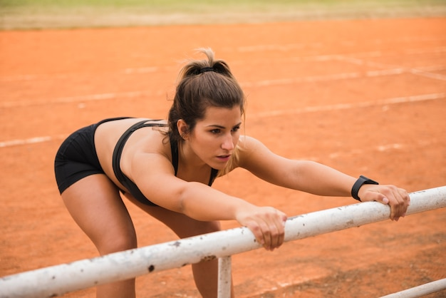 Sporty woman stretching on stadium track