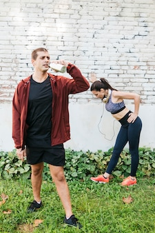 Sporty woman stretching in urban environment with man behind