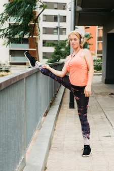 Sporty woman stretching in urban environment