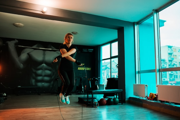 Sporty woman training with jump rope in gym.