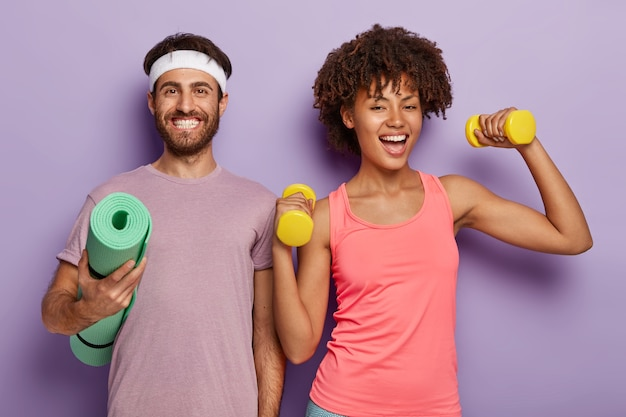 Sporty woman trains with dumbbells, has cheerful look, her husband stands near, holds rolled up fitness mat, isolated on purple background