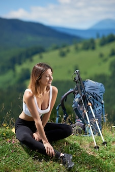 Sporty woman traveller with backpack and trekking poles relaxing after hiking on the top of a hill, enjoying sunny day in the mountains