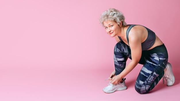 Спортивная женщина, завязывающая шнурки для обуви в студии на розовом фоне