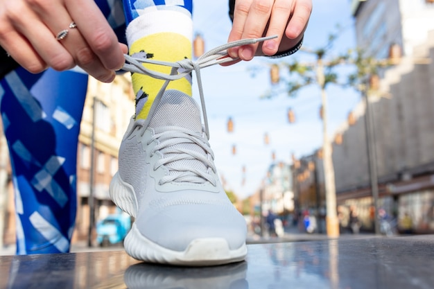 Sporty woman tying shoelace on sneakers before training. female athlete preparing for jogging outdoors. runner getting ready for morning running routine. sport active lifestyle concept. close-up