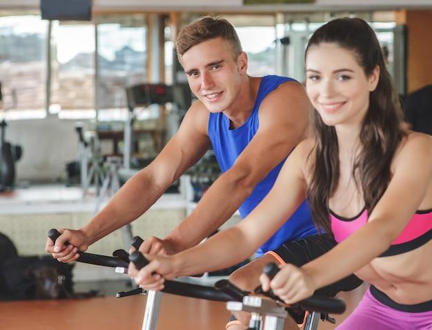 彼女のフィットネスパートナーとサイクリングエアロバイクを使用してスポーティな女性