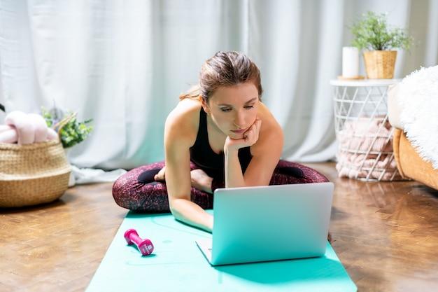 Спортивная женщина, используя свой ноутбук во время тренировки дома.