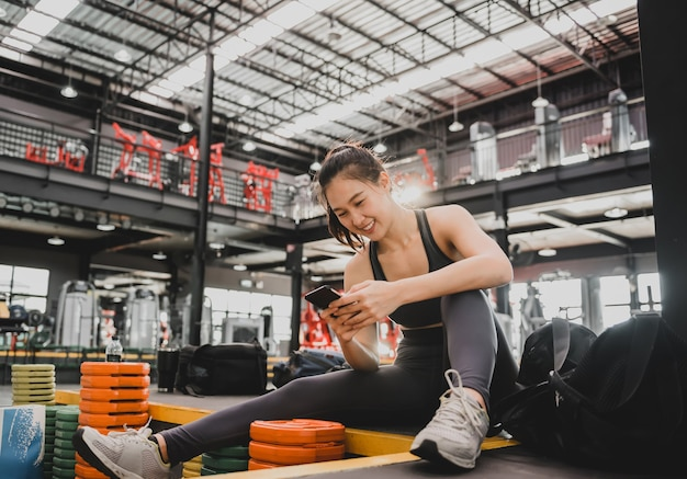 トレーニング後に携帯電話を使用するスポーティな女性。フィットネスジムでのアジアの女性の運動とライフスタイル。ボディービルのための健康と健康。