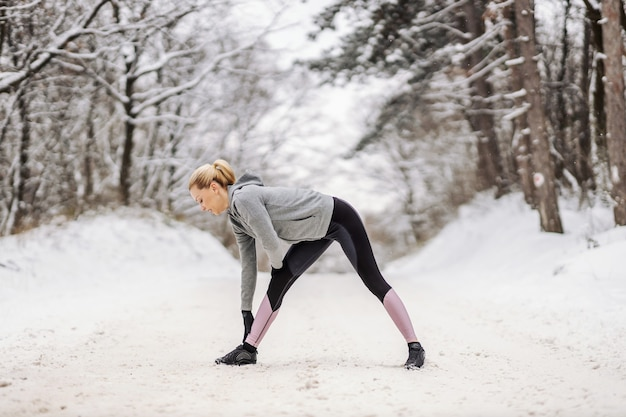 Sporty woman in warm sportswear doing warm up exercises at snowy winter day in nature.