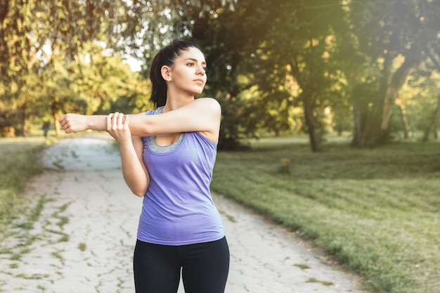 Sporty woman warming up before workout, yoga or fitness outdoor in sunrise or sunset.