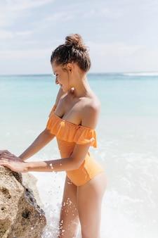 Спортивная женщина носит ретро купальник трогательно морской скалы. открытый портрет романтичной загорелой дамы с милой прической, стоящей на берегу океана.