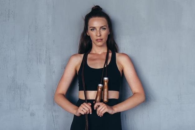 Спортивная женщина со скакалкой смотрит в камеру.