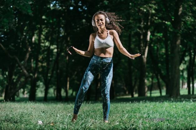도시 공원에서 스마트폰 춤을 추는 스포티한 여성