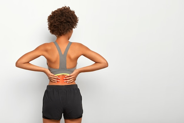 Sporty woman with afro haircut touches waist with both hands, feels pain in spine, shows location of inflammation, wears grey top