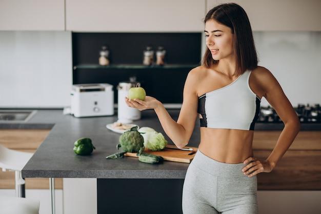 Спортивная женщина с яблоком на кухне