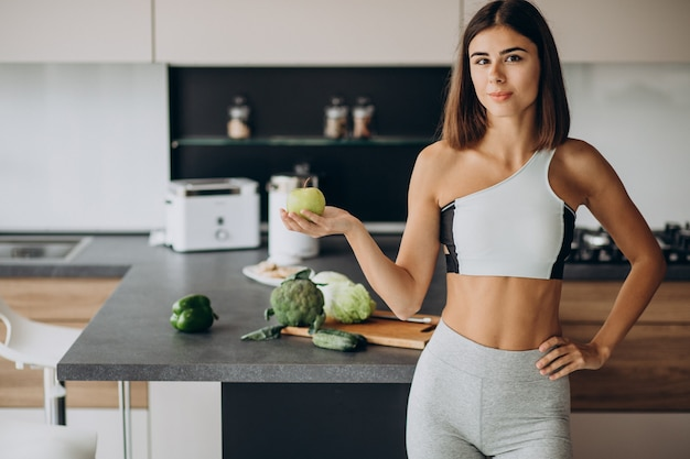 Sporty woman with apple at the kitchen