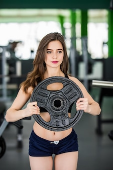 Sporty woman with barbell cargo works in gym alone