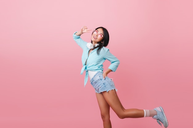 Sporty woman with bronze skin funny dancing with positive face expression. graceful latin girl in blue attire posing on one leg.